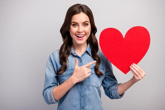 Zdjęcie całkiem zabawnej damy wskazuje palec duże czerwone papierowe serce świętuje dzień zakochanych fajne zaproszenie nietypowy pomysł nosić dżinsy na co dzień koszula dżinsowa na białym tle szary kolor