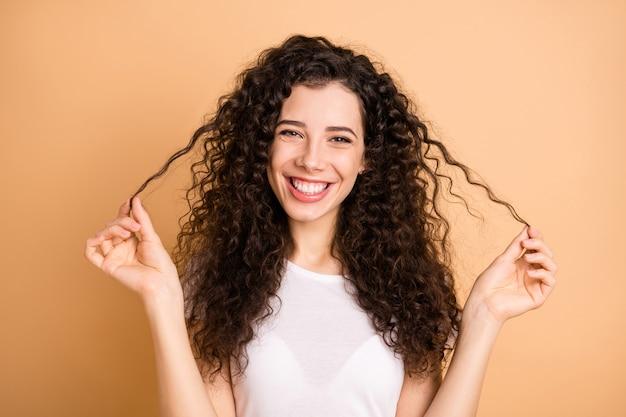 Zdjęcie całkiem zabawnej pani pokazującej idealne faliste loki po trwałej ondulacji po wizycie w ulubionym salonie fryzjerskim nosić białe codzienne ubrania na białym tle beżowym pastelowym kolorze