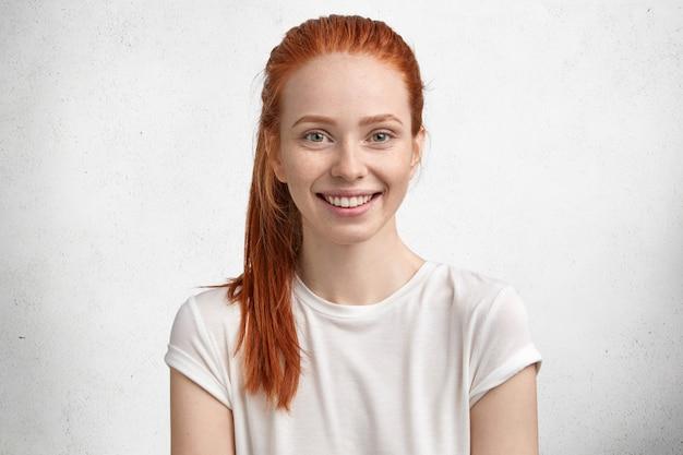 Zdjęcie całkiem zadowolonej rudej suki, ma zielone oczy, piegowatą cerę, miło się uśmiecha, jest na duchu i spędza wolny czas w rodzinnym gronie