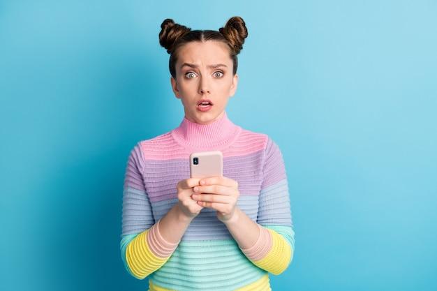 Zdjęcie całkiem zdziwionej zszokowanej nastolatki dwie ładne bułeczki wpływowy freelancer przytrzymaj telefon czytaj zwolenników komentarze zły nastrój nosić pasiasty sweter na białym tle niebieski kolor tła