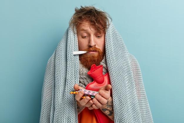 Zdjęcie chorego rudego mężczyzny czuje się chory, ma wirusa grypy zimowej, ma gorączkę i wysoką temperaturę, trzyma termometr w ustach, zawinięty w kołderkę, ogrzewa gorącą butelką, ma różne leki