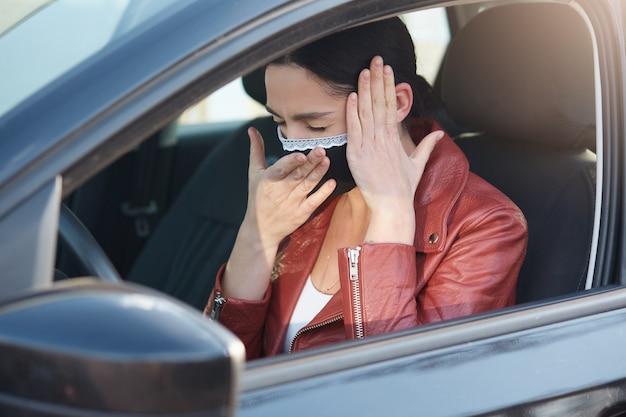 Zdjęcie chorej młodej kobiety, kichającej i kaszlącej, zamykającej oczy, bóle głowy, zakrywającej usta dłonią