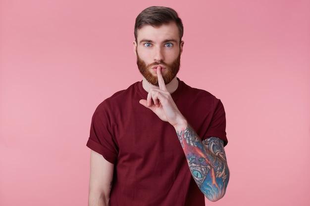 Zdjęcie cichego, poważnego, spokojnego brodatego mężczyzny z wytatuowaną ręką pokazującą ciszę, prosi o zachowanie tajemnicy, prywatności, milczenie, cicho kładąc palec wskazujący na ustach, na różowym tle.