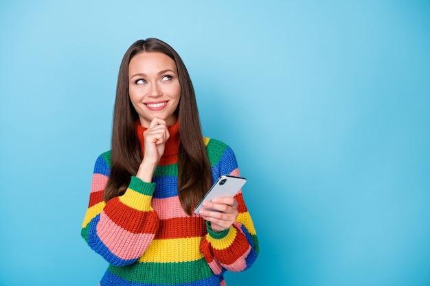 Zdjęcie ciekawa dziewczyna uzależniona od blogera używać smartfona myśleć myśli wyglądać copyspace dotknąć palce podbródek zdecydować, co pisać pisanie nosić tęcza styl sweter na białym tle niebieski kolor tła