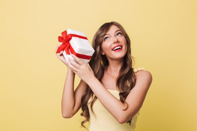 Zdjęcie ciekawej szczęśliwej kobiety w wieku 20 lat, mającej długie brązowe włosy, uśmiechającej się i potrząsającej pudełkiem prezentowym, aby dowiedzieć się, co jest w środku, odizolowane na żółtym tle
