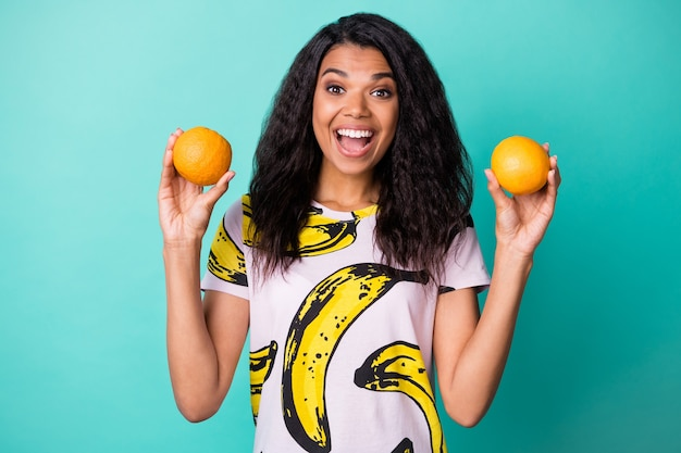 Zdjęcie czarnej dziewczyny trzyma dwie pomarańcze otwarte usta wyglądają na aparat nosić bananową koszulkę z nadrukiem na białym tle turkusowy kolor