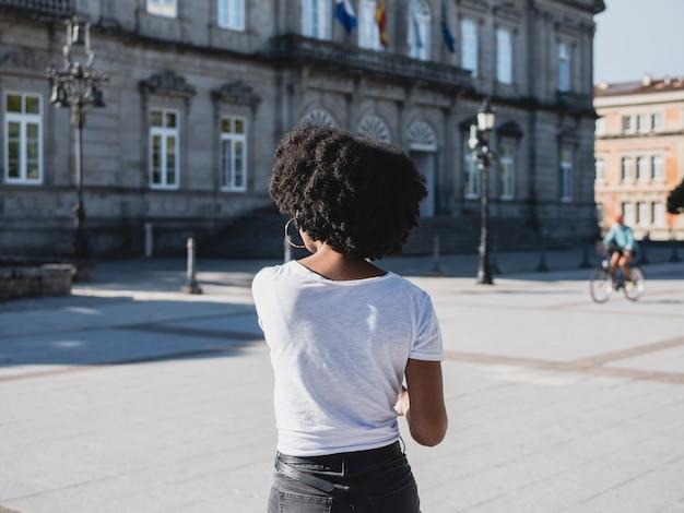 Zdjęcie czarnej dziewczyny zrobione z tyłu, na ulicy