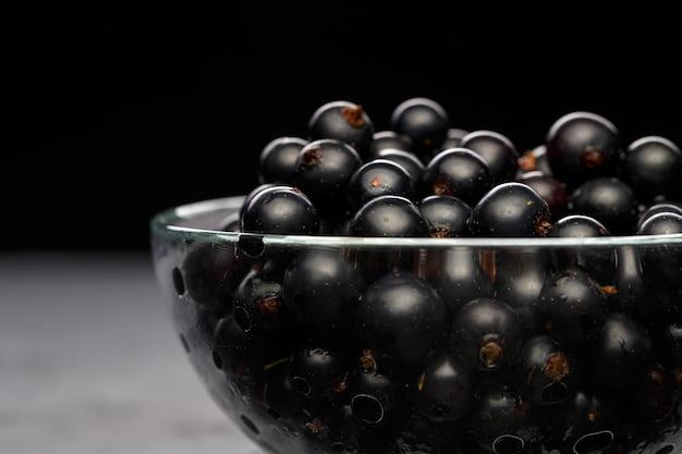 Zdjęcie czarnej porzeczki w szklanej przezroczystej filiżance na czarnej pustej ścianie