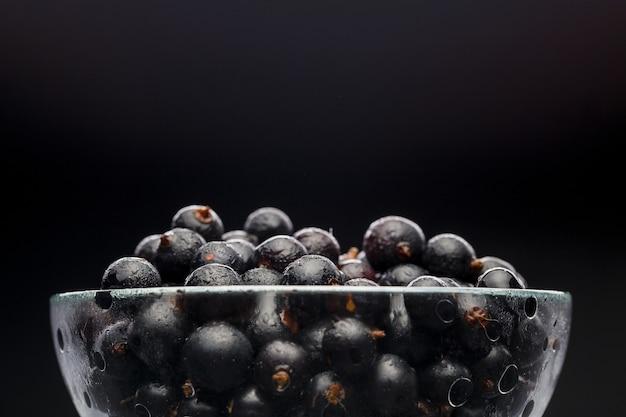 Zdjęcie czarnej porzeczki w szklanej przezroczystej filiżance na czarnym pustym tle