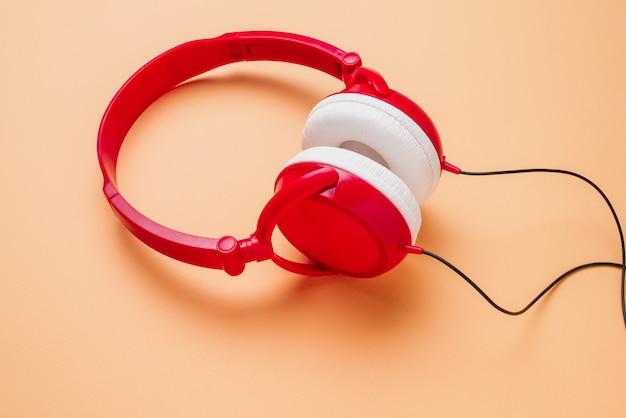 Zdjęcie czerwieni z białymi słuchawkami na brzoskwiniowym tle