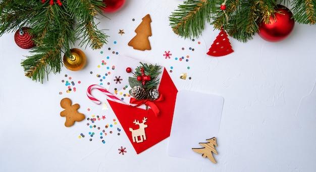 Zdjęcie czerwonej koperty, ciasteczka, gałęzie świerkowych ozdób choinkowych na pustym białym tle