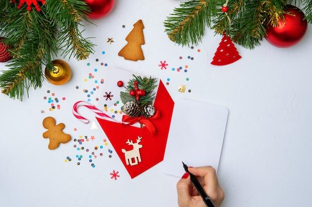 Zdjęcie czerwonej koperty świąteczne, ciasteczka, ręce z piórem, gałęzie świerku ozdoby świąteczne na pustym białym tle