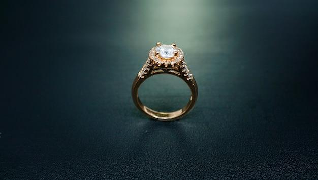 Zdjęcie damskiego złotego pierścionka ozdobionego błyszczącym diamentem
