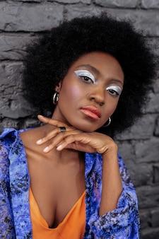 Zdjęcie dla magazynu o modzie. ciemnowłosa piękna modelka z jasnym makijażem wygląda ładnie