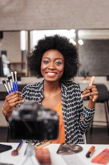 Zdjęcie dla magazynu o modzie. śliczna kobieta z kręconymi włosami czuje się niesamowicie podczas robienia zdjęć do magazynu o modzie