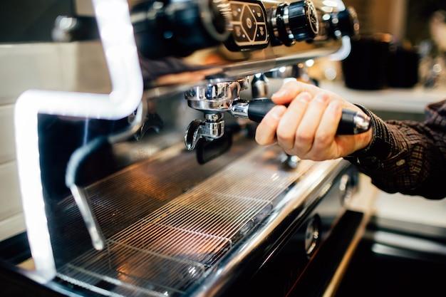 Zdjęcie dłoni mężczyzny trzymającego cezve z ekspresu do kawy zablokowane i parzenia kawy.