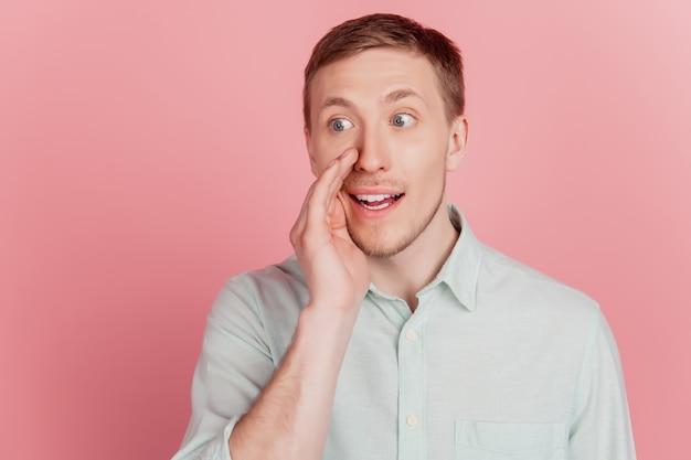 Zdjęcie dłoni młodego mężczyzny w pobliżu ust szeptem powiedz mów sekretny wygląd pustej przestrzeni izolowanej nad różowym kolorem tła