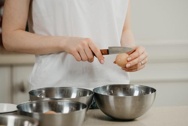 Zdjęcie dłoni młodej kobiety, która nożem rozbija skorupkę jajka z ekologicznej farmy nożem nad miską na zupę ze stali nierdzewnej w kuchni
