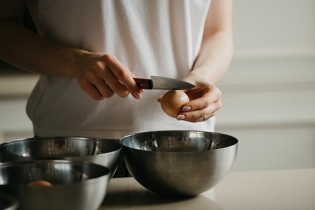 Zdjęcie dłoni młodej kobiety rozbijającej skorupkę nożem nad miską ze stali nierdzewnej w kuchni