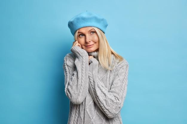 Zdjęcie dobrze wyglądającej kobiety w średnim wieku ma rozmarzoną, zamyśloną minę, nosi przytulny zimowy szary sweter i niebieski beret, optymistycznie oczekując wyjścia w deszczowy jesienny dzień
