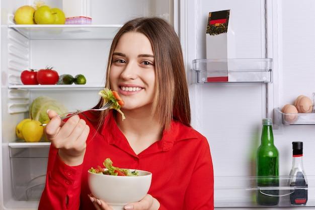 Zdjęcie dobrze wyglądającej młodej kobiety o przyjemnym wyglądzie stoi w pobliżu otwartej lodówki z miską sałatek, je tylko zdrowe jedzenie, będąc w dobrym nastroju. ludzie, jedzenie, weganie i styl życia