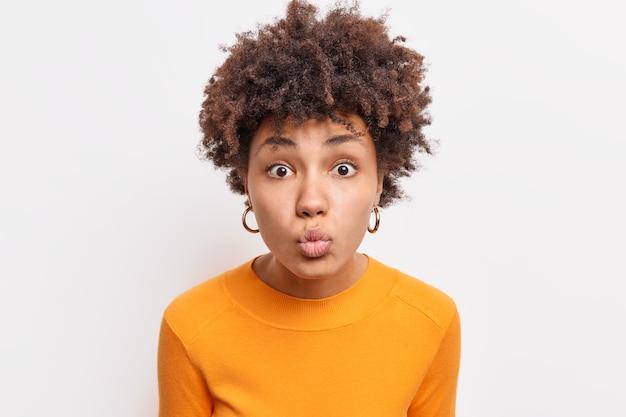 Zdjęcie Dobrze Wyglądającej Młodej Kobiety Z Kręconymi Włosami Trzyma Złożone Usta Chce Się Pocałować Ktoś Nosi Casual Pomarańczowy Sweter Wygląda Uważnie Na Białym Tle Nad Białą ścianą. Wyrazy Twarzy Premium Zdjęcia
