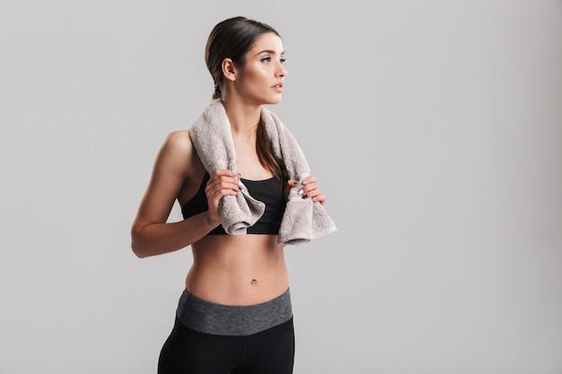Zdjęcie dobrze zbudowanej kobiety fitness w sportowej pozowanie ręcznikiem na szyi i patrząc na bok w siłowni, na białym tle nad szarej ścianie