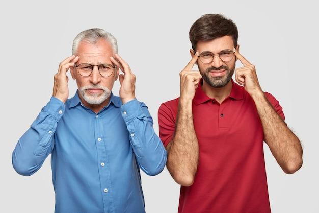Zdjęcie dojrzałego europejczyka i jego niedoświadczonego męskiego asystenta ma migrenę