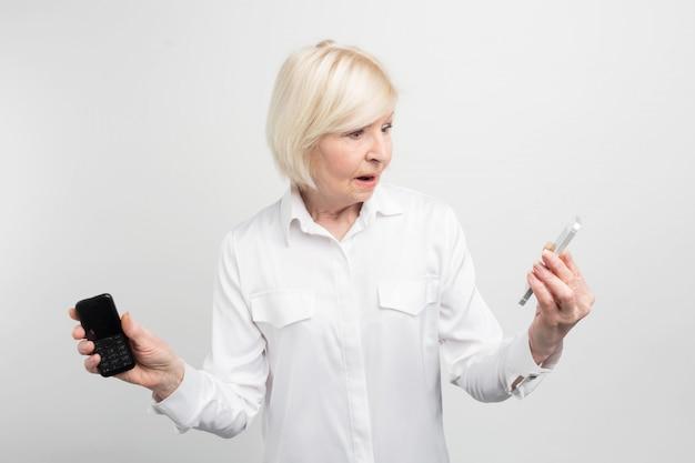 Zdjęcie dojrzałej kobiety trzymającej w ręku dwa telefony. używała telefonu ld. kobieta nie wie, jak korzystać z nowego telefonu. wygląda dość nietypowo.