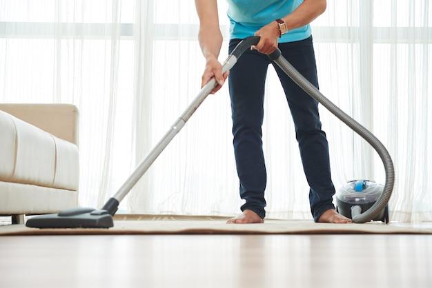 Zdjęcie dolnej części ciała nierozpoznawalnego mężczyzny odkurzającego dywan w domu
