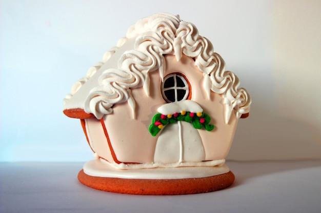 Zdjęcie domu ciasteczek imbiru santa na białym tle. dekoracja świąteczna