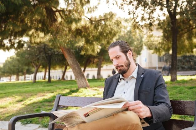 Zdjęcie dorosłego przystojny mężczyzna w garniturze siedzi na ławce w zielonym parku i czyta gazetę w słoneczny dzień