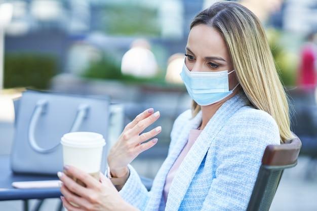 Zdjęcie dorosłej, atrakcyjnej kobiety w masce pijącej kawę w mieście