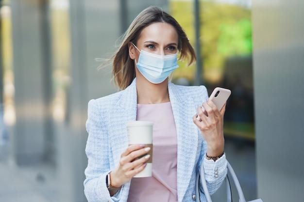 Zdjęcie dorosłej, atrakcyjnej kobiety w masce ze smartfonem spacerującej po mieście