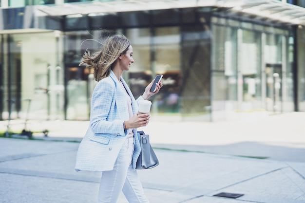 Zdjęcie dorosłej, atrakcyjnej kobiety ze smartfonem spacerującej po mieście
