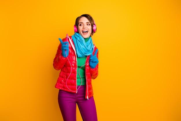 Zdjęcie dość podekscytowanej pani trzymaj inteligentny telefon słuchaj słuchawek taniec impreza chłodny nastrój nosić dorywczo czerwony płaszcz niebieski szalik rękawiczki spodnie
