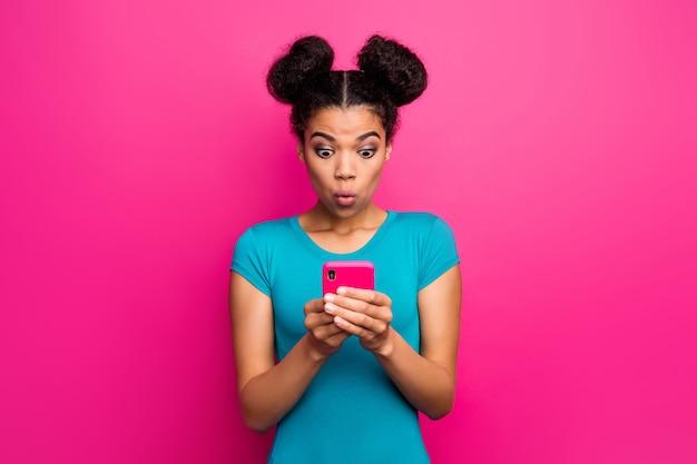 Zdjęcie dość zszokowanej ciemnej skóry pani trzyma telefon z otwartymi ustami