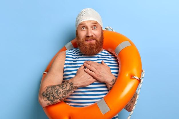 Zdjęcie dotkniętego wrażeniem mężczyzny trzyma dłonie blisko serca, obiecuje coś żonie, nosi gumową czapkę i marynarską kamizelkę w paski