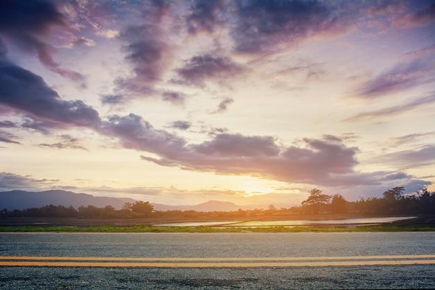 Zdjęcie drogi z zachodem słońca. krajobraz w okresie letnim w tajlandii