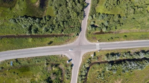 Zdjęcie drona skrzyżowania drzew w kolorowej wczesnej wiośnie - widok z góry na dół ze świeżo uprawianym polem po jednej stronie i polem mniszka lekarskiego po drugiej stronie