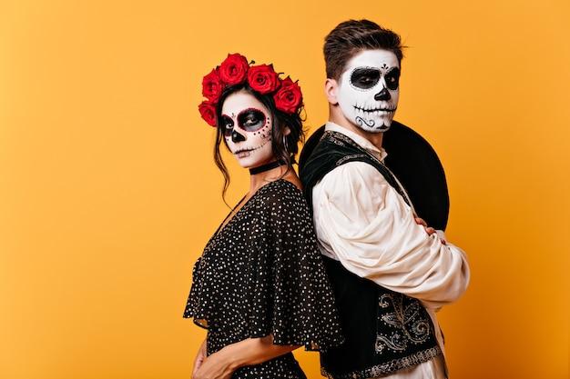 Zdjęcie dumnej meksykańskiej pary w tradycyjnych strojach z pomalowanymi twarzami. dziewczyna z różami we włosach pozuje z młodym mężczyzną z sombrero za plecami.