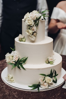 Zdjęcie dużego, białego, trzystopniowego ciasta z pysznymi kwiatami