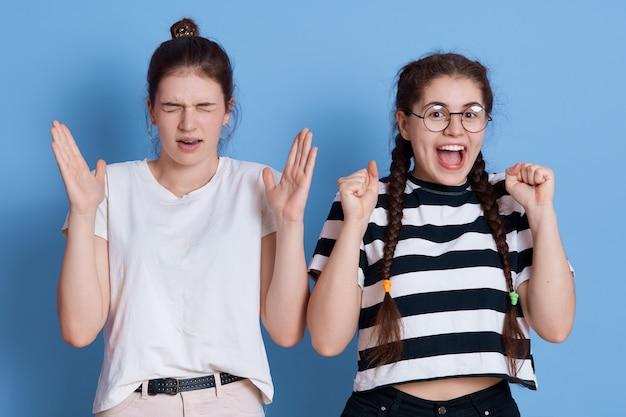 Zdjęcie dwóch emocjonalnych przyjaciółek w casualowych koszulkach