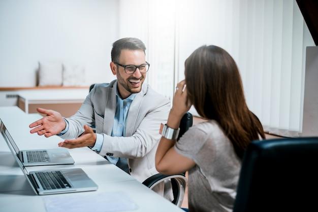 Zdjęcie dwóch kolegów omawiających projekt w biurze.
