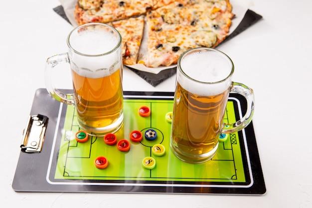 Zdjęcie dwóch kufli piwa, piłkarzyki, pizza na białym stole