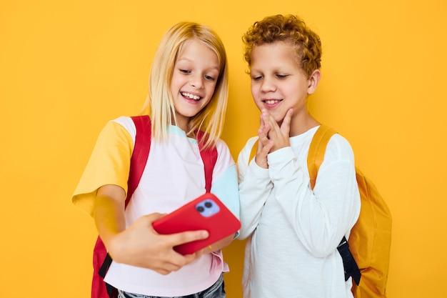 Zdjęcie dwóch małych dzieci dziewczyna mówi i uśmiecha radość emocje studio koncepcja edukacji. zdjęcie wysokiej jakości