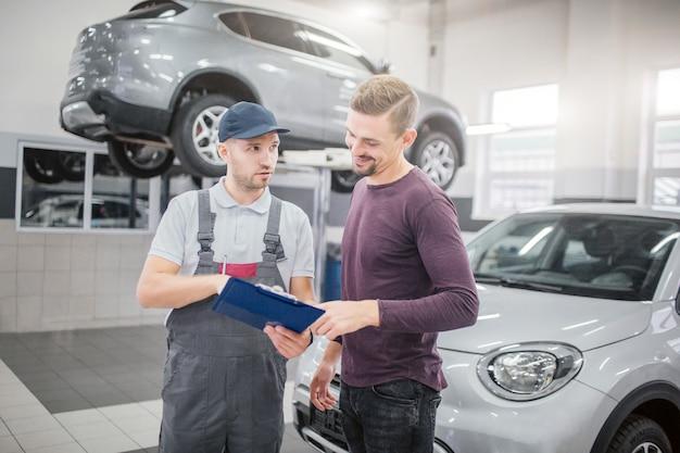 Zdjęcie dwóch młodych mężczyzn stojących razem w garażu. brodaty facet uśmiecha się i wskazuje na plastikowej tabliczce z dokumentami. mężczyzna w szarym mundurze i czapce rozmawiają i patrzą na klienta. on jest poważny.