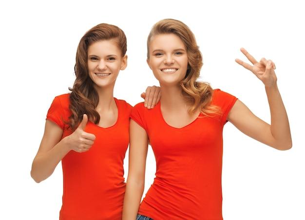 Zdjęcie dwóch nastoletnich dziewcząt pokazujących kciuk w górę i znak zwycięstwa