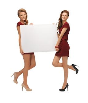 Zdjęcie dwóch nastoletnich dziewcząt w czerwonych sukienkach z pustą tablicą