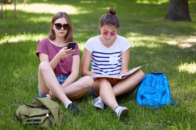 Zdjęcie dwóch nastoletnich kobiet siedzi na zielonej trawie na zewnątrz, czyta książkę i używa telefonu komórkowego do surfowania w sieciach społecznościowych, nosi okulary przeciwsłoneczne